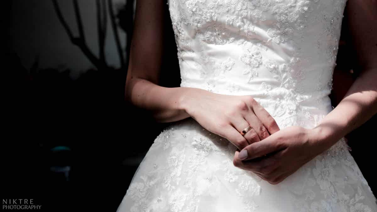 Eine Frau im Brautkleid hält Hände vor dem Bauch und zeigt ihren Ehering