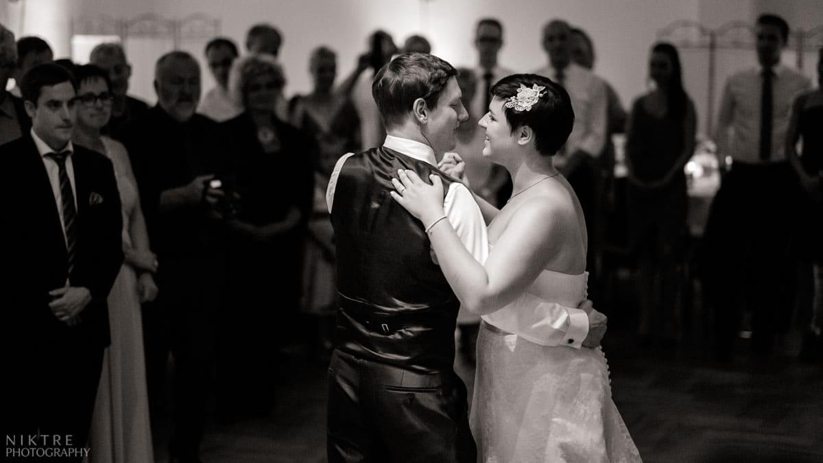 Das Brautpaar beim Hochzeitstanz zum Lieblingslied mit Gästen im Hintergrund