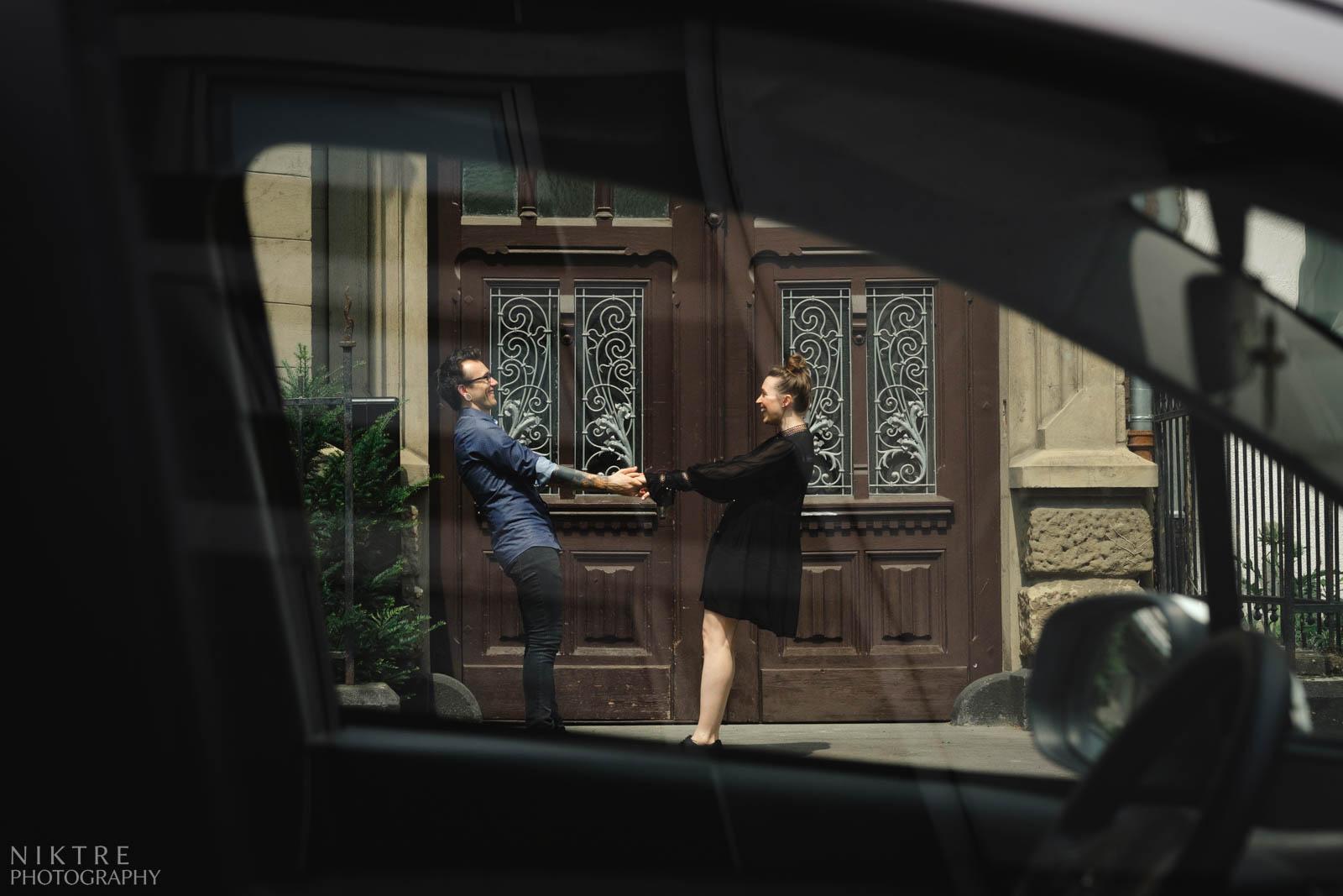 Ein Foto durch ein Autofenster auf dem ein Mann und eine Frau die Hände halten