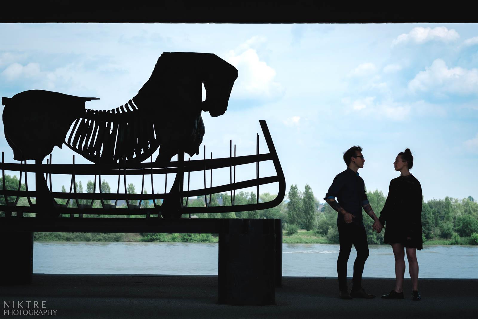 Silhouetten von zwei Menschen und eines Pferdes mit Rhein im Hintergrund