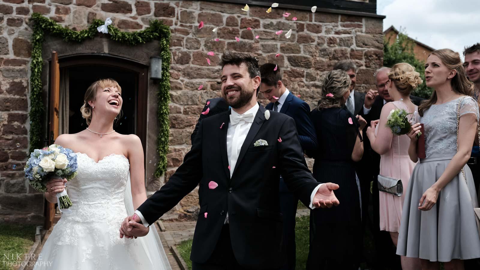 Braut und Bräutigam unter geworfenen Blütenblätter nach der Kirche