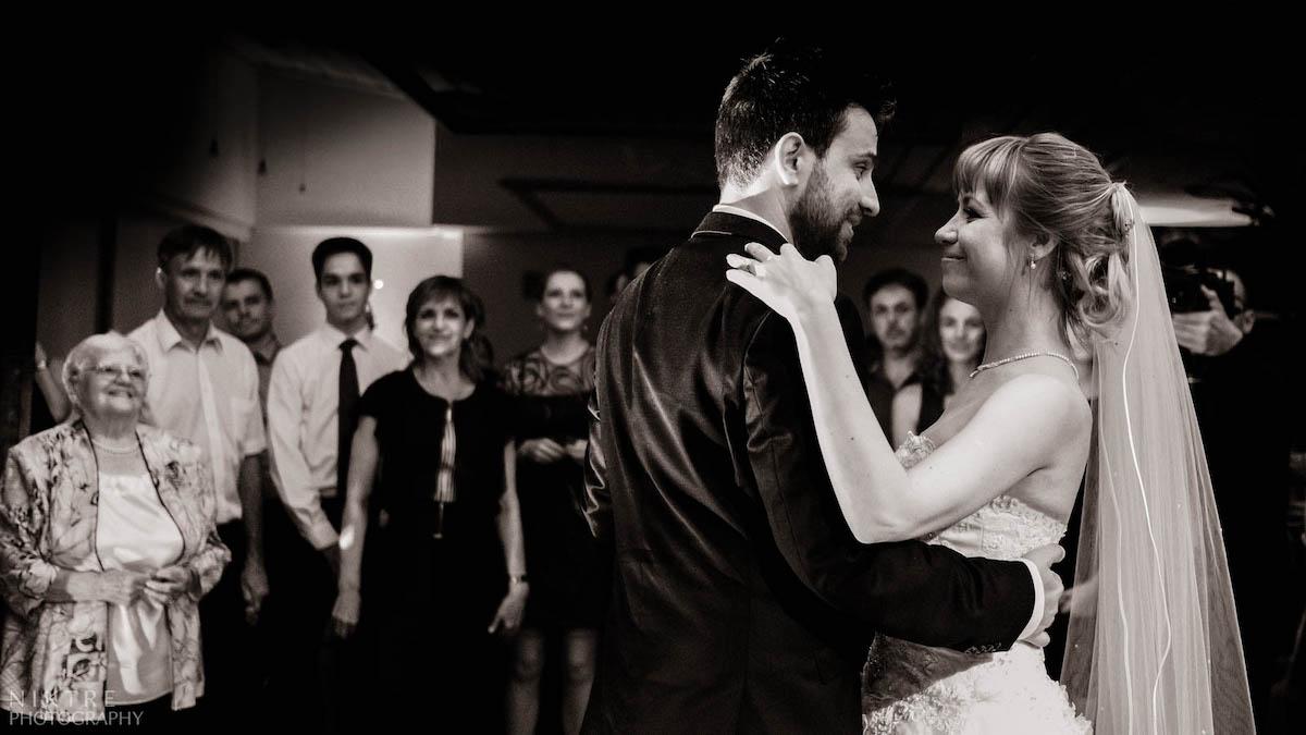 Das Brautpaar wird von Gästen beim ersten Tanz beobachtet