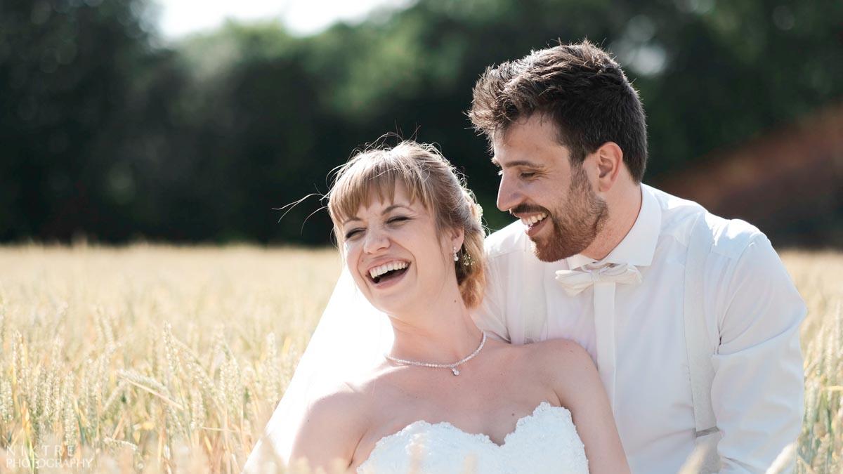 Braut und Bräutigam lachen um Weizenfeld