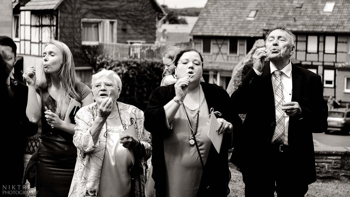 Gäste sind aufgeregt und warten auf das Brautpaar mit Seifenblasen