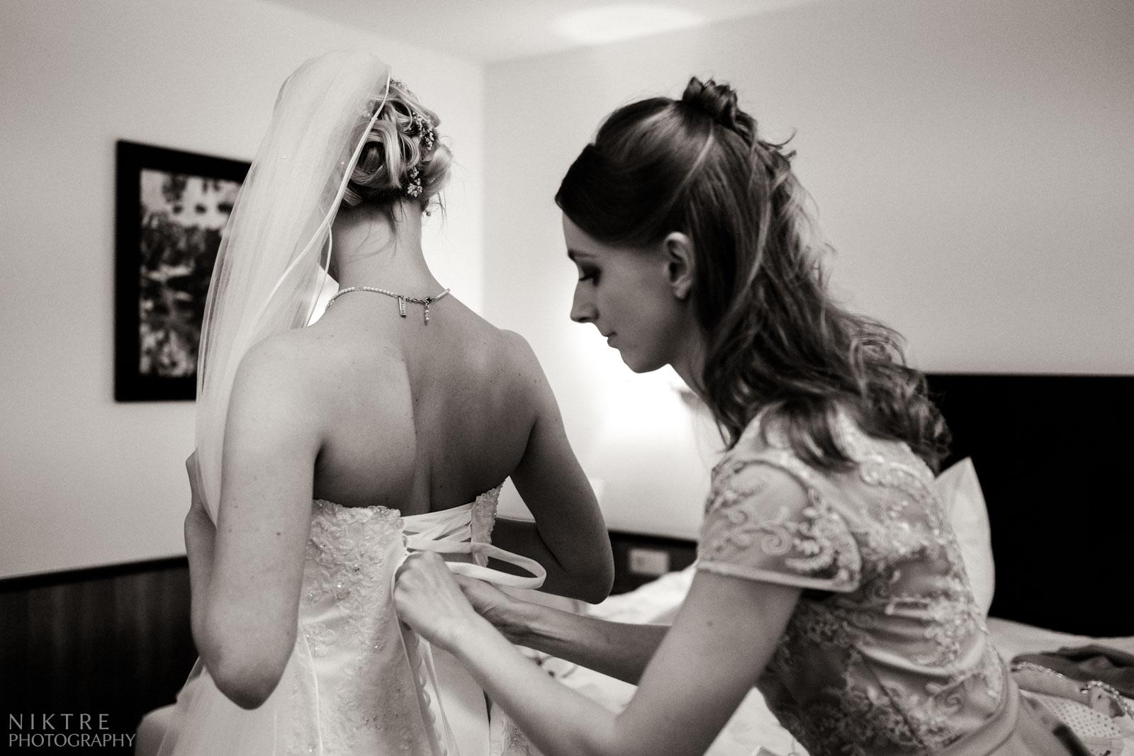 Die Trauzeugin hilft mit dem Brautkleid