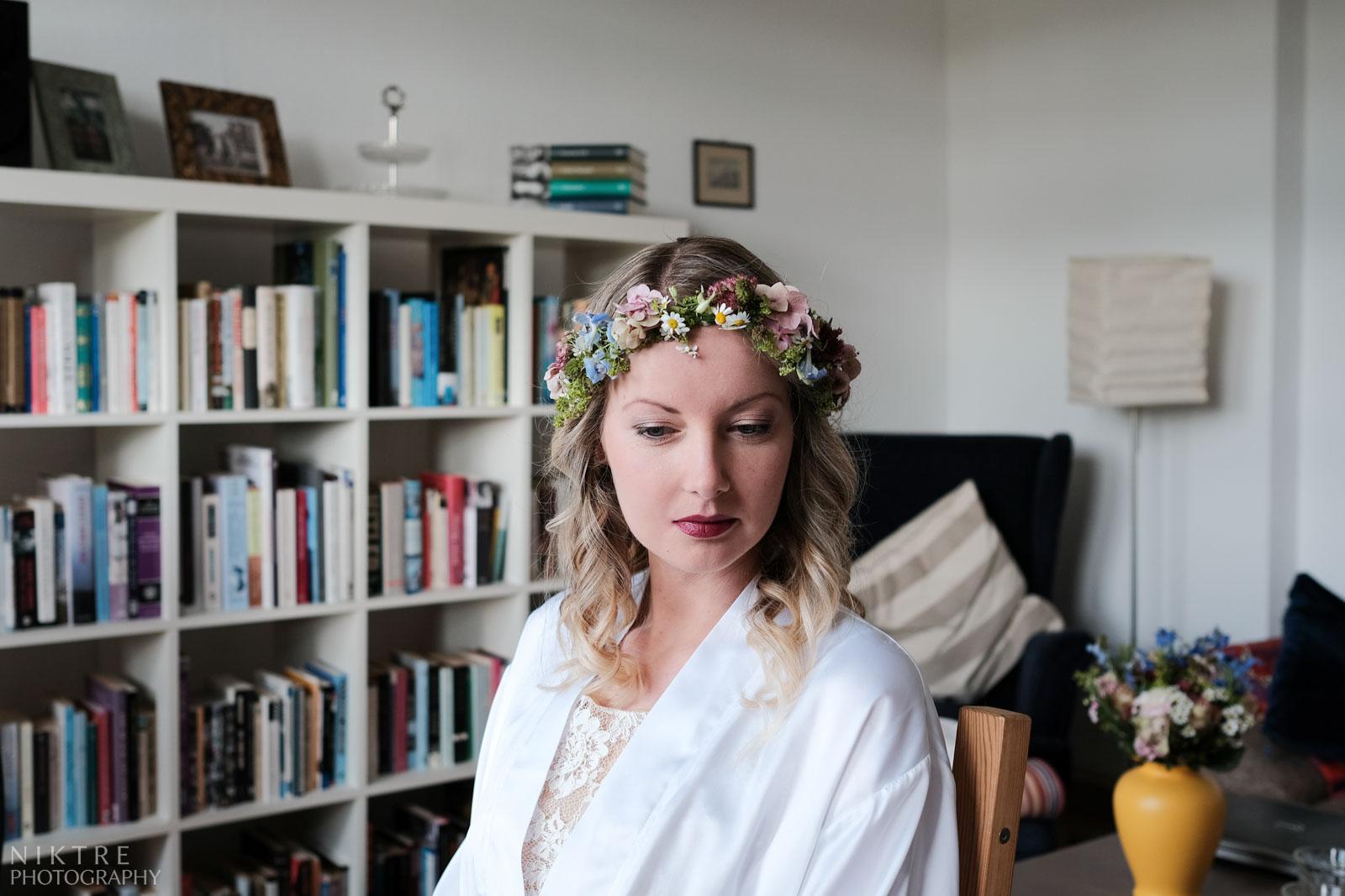 Die Braut sitzt in einem aufgeräumten Zimmer beim Getting Ready