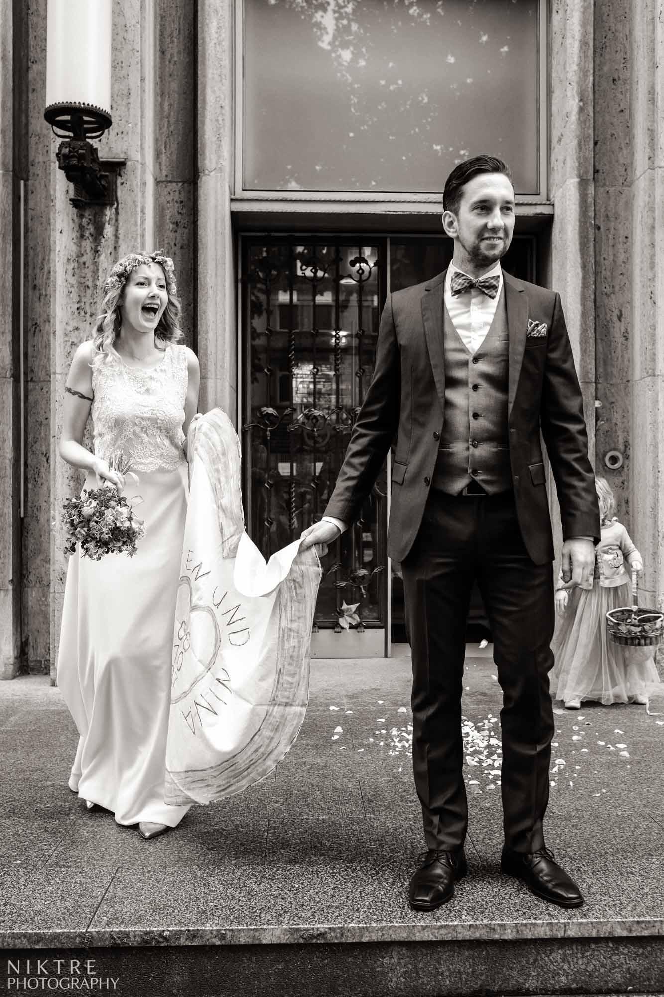 Braut lacht über das süße Blumenmädchen