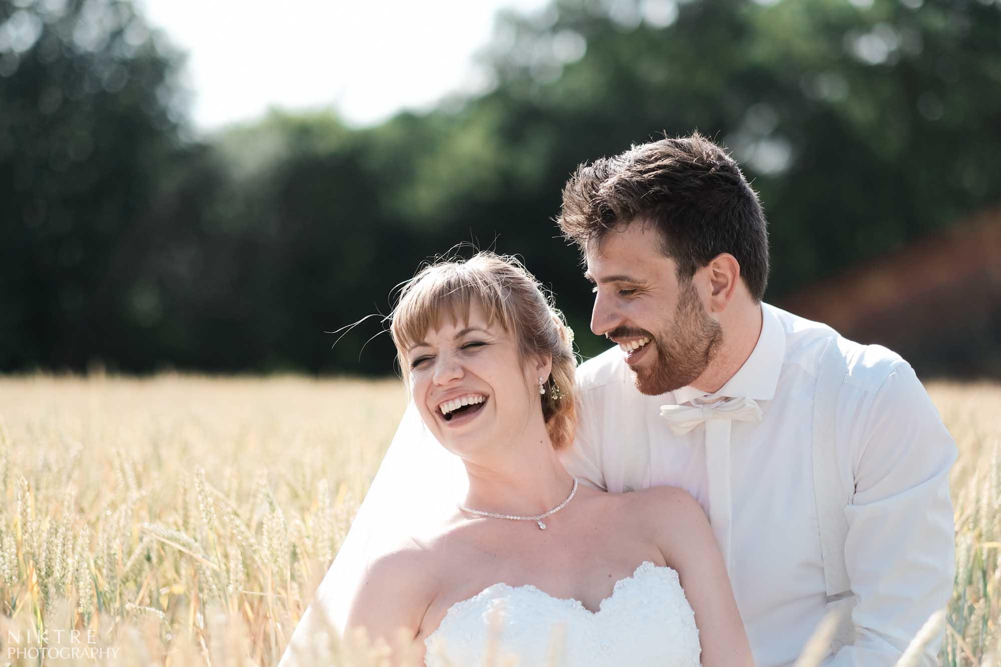 Brautpaar lacht beim Hochzeitsshooting im Weizenfeld nahe Göttingen
