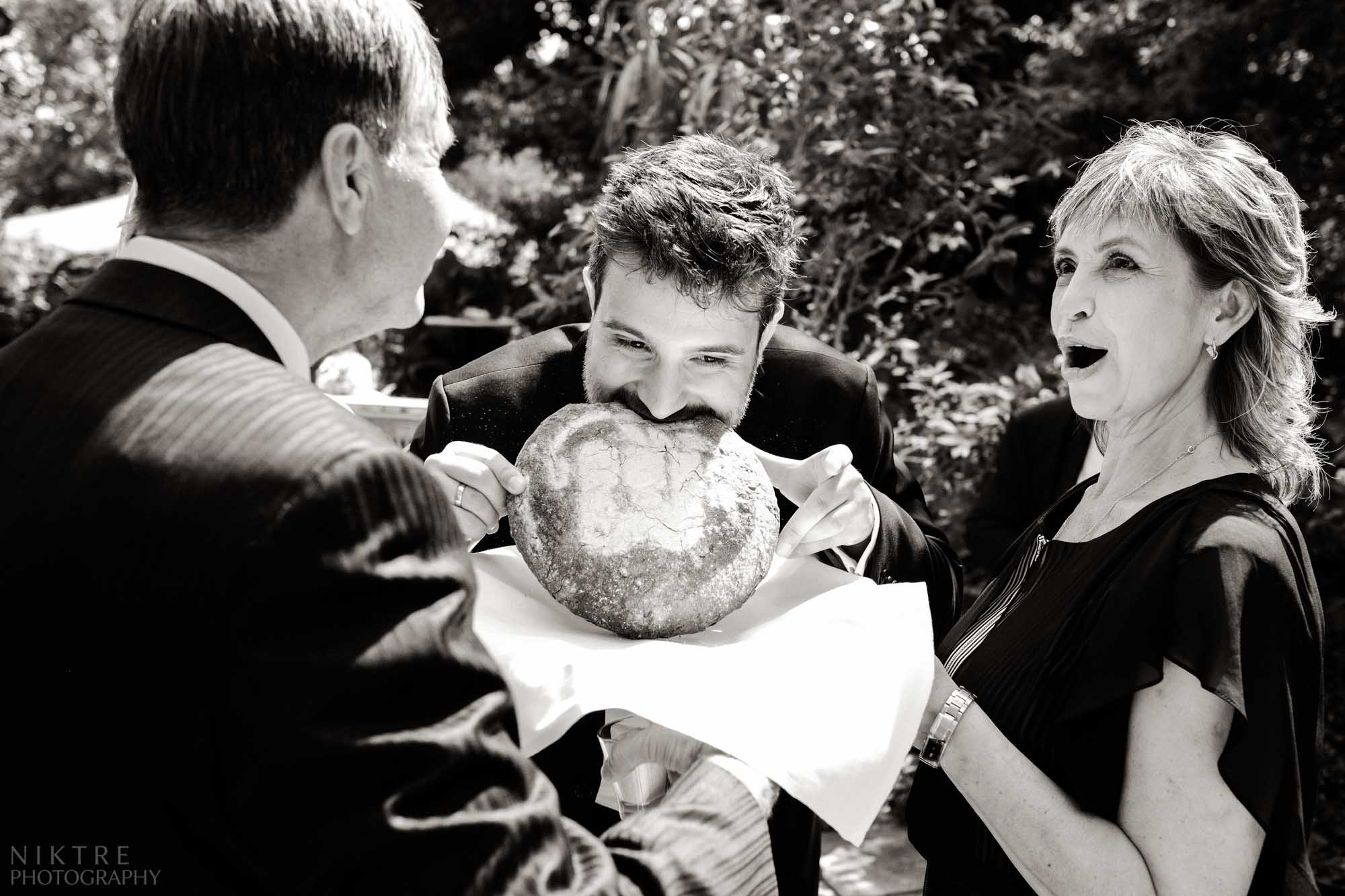 Hochzeitsreportage zeigt Emotionen des Bräutigams beim Abbeißen des Brotes