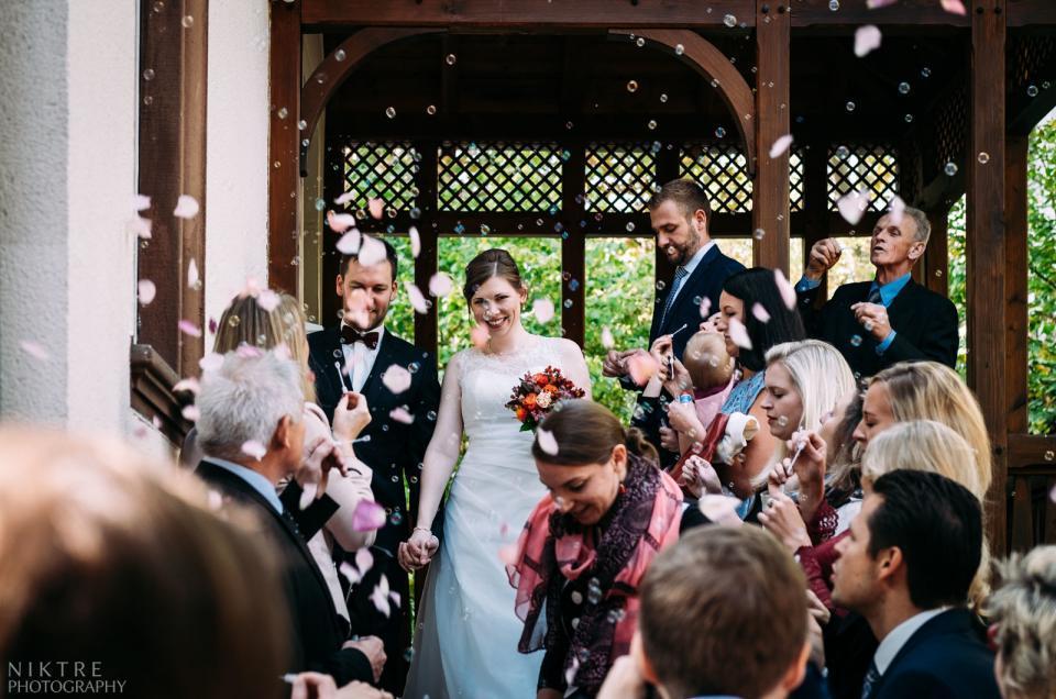 Das Traumpaar nach der Trauung spaziert durch Konfetti aus Rosenblätter und Seifenblasen
