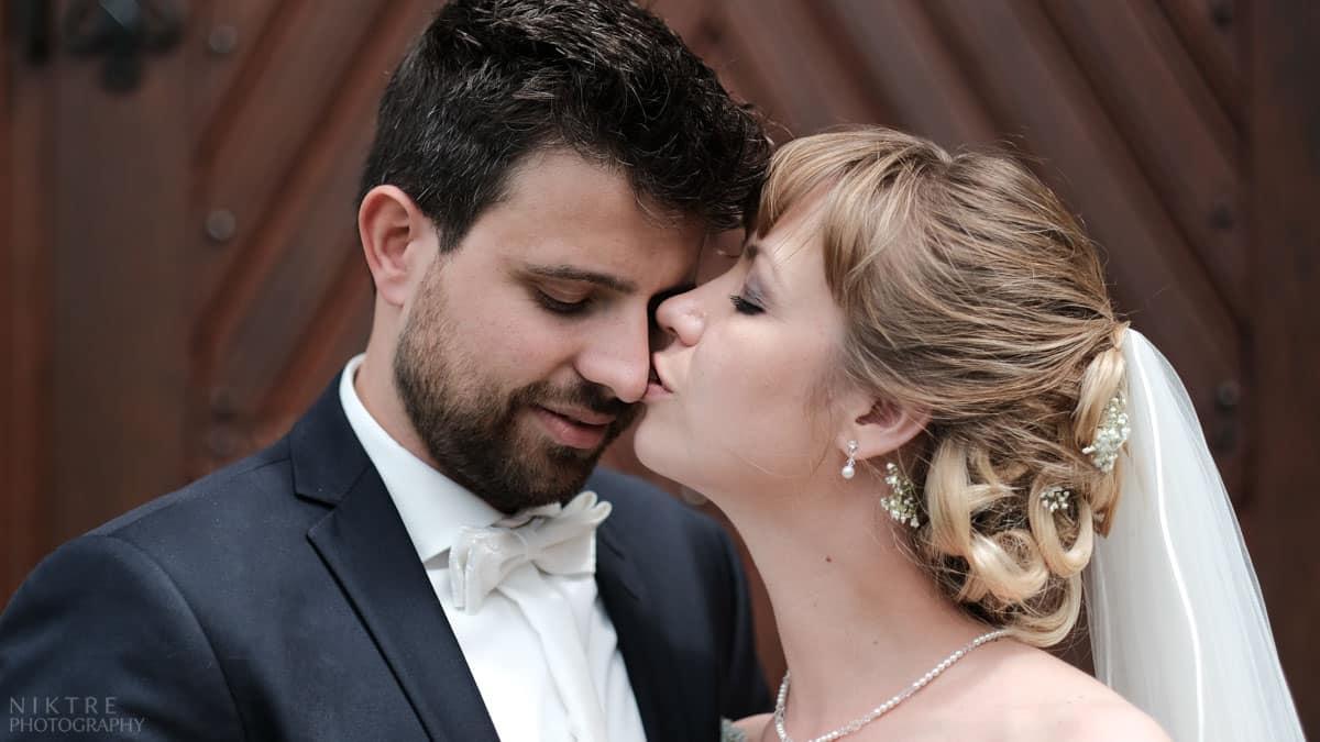 Hochzeitsfotograf Mainz zeigt die Braut, die den Bräutigam vor der Kirche küsst